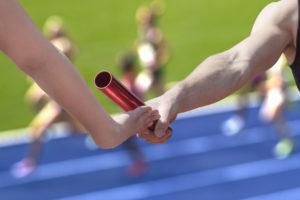 29300720 - male relay runner hands over the red baton to female runner